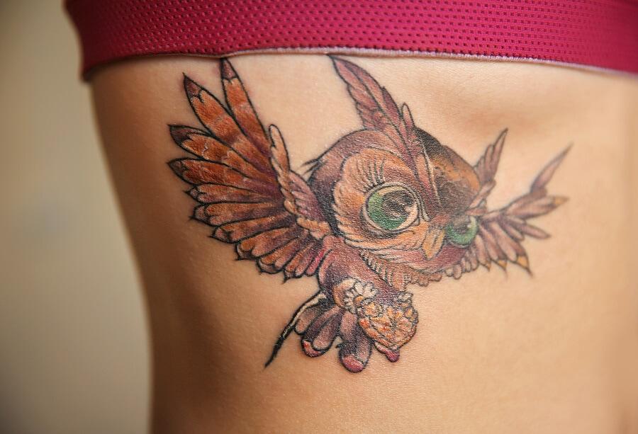 Owl tattoo on woman ribs