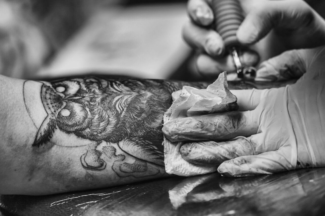 Man getting owl tattoo